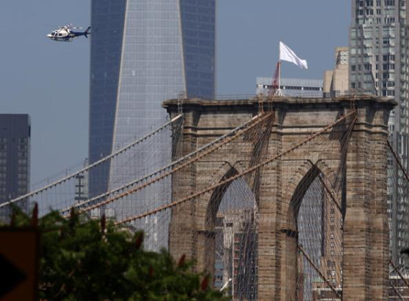 Un helicóptero de policía de Nueva York vuela sobre el puente de Brooklyn inspeccionando las banderas blancas que aparecieron en la parte superior. La policía investiga quién retiró las banderas americanas y los cambió durante la noche. (EPA/ANDREW GOMBERT)